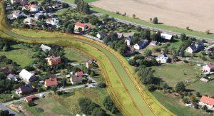 Obec Zátor, letecký pohled proti toku na úsek mezi silničním mostem v km 82.510 dle TPE a revitalizací v dolní části obce - po realizaci úprav (zvýrazněné kontury navrhovaných konstrukcí)